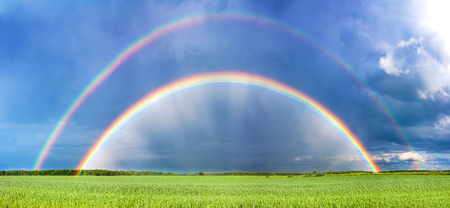 beautiful spring landscape panorama with a field and a rainbow above it. double rainbow shines in the sky, panoramic view