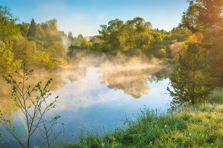 amazing beautiful spring landscape with fog and river at sunrise. sunny scenery early morning view of river and forest