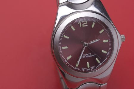 chrome man: Close up of a men sport watch on a red background