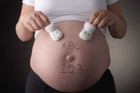 seven month pregnant belly with ABC and 123 written with  shoes