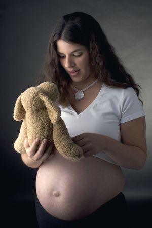 Seven month pregnant women talking to a stuff dog