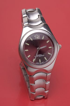 chrome man: Men sport watch on red reflecting surface Stock Photo