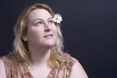 Vrouwen zoeken naar de hemel te denken over de bloem in haar haar Stockfoto
