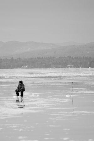 쓴 겨울의 한가운데에있는 솔리테어 얼음 피셔 맨