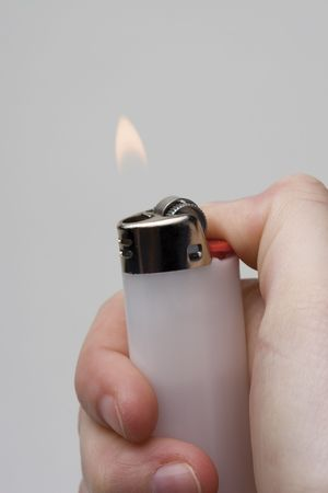 Women hand holding a white lighter with flame on white background