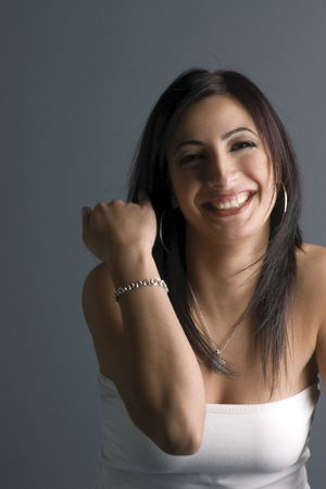Twenty something fashion model in white tube top, showing bracelet or making a rude gesture laughing