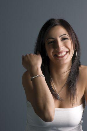 Twintig iets fashion model in witte buis boven, blijkt armband of een onbeleefd gebaar lachen