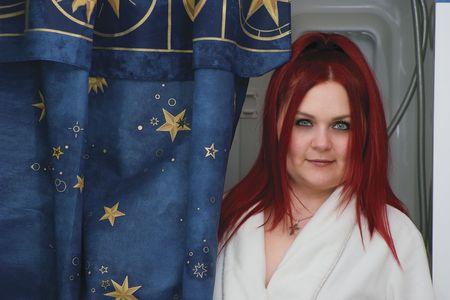 Red hair woman model in white bathrobe standing in bathroom