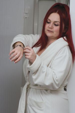 Red hair woman model in white bathrobe standing in bathroom playing with bracelet