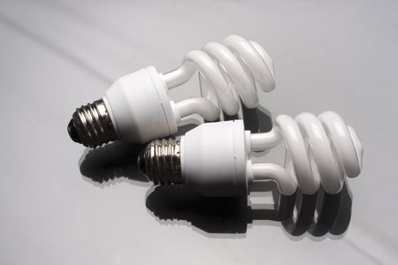 two compact fluorescent light bulb on reflective surface Banco de Imagens