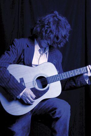 Jonge mannelijke model in een pak spelen akoestische gitaar. Duotoon blauw schilderij met ingang