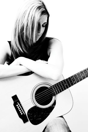 Thirty something women sitting on stule leaning on accoustic guitar looking down Stock Photo