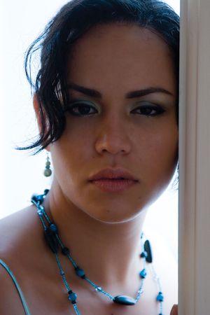 Twintig iets latino vrouwen met haar hoofd leunend op een deur frame