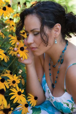 Twenty something latino women with her eyes close, smeling yellow daisies in a garden