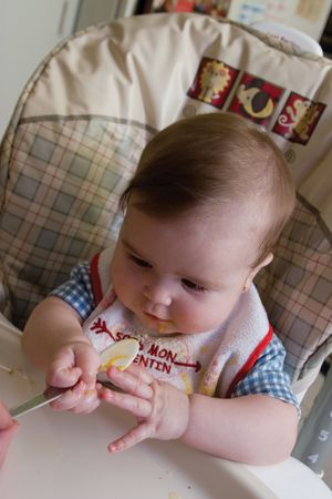 Six months baby girl fighting to get a spoon with food photo