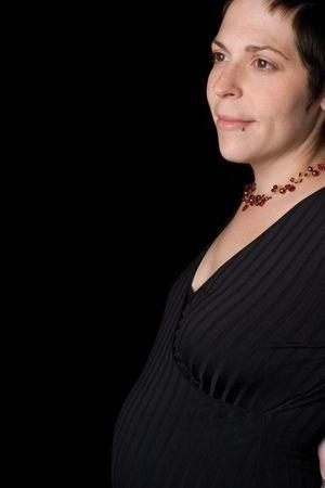 profile portrait of a late twenty pregnant women with head turn toward the camera