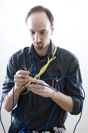 a clueless network technician looking at wires Imagens