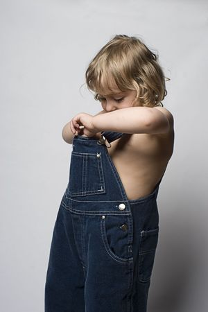 overall: Two year old toddler searching in his jean overall