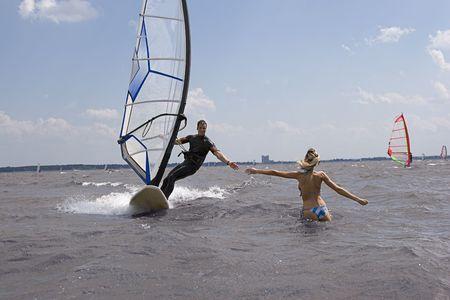 Windsurfer komen op volle snelheid met de hand reiken naar vriendin