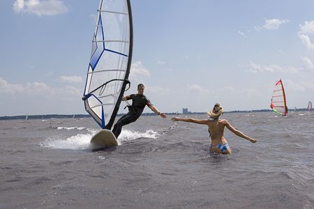 windsurfer coming in at full speed with hand reaching for girlfriend Archivio Fotografico