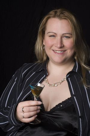 Portrait of a thirty something overweight women in evening clothes having a drink of brown rum