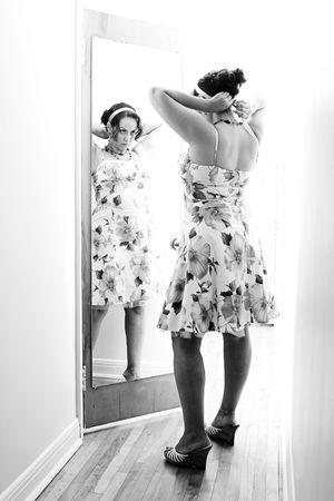 Twintig iets vrouwen aanpassing hand band in front of a mirror hechten aan een deur
