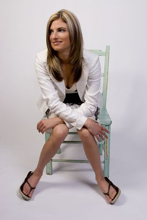 hooked up: Thirty something business women in suit and sandals sitting on country style chair Stock Photo