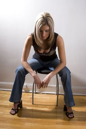 thirty something: Thirty something women dress sitting on a stool with her head down, taking a moment to relax