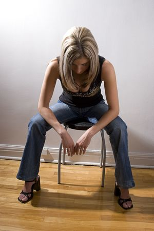thirty something: Thirty something women dress in rocker style, sitting on stool looking at the floor