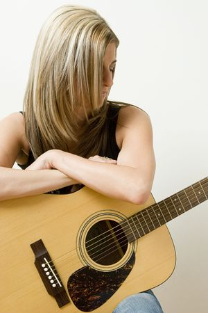 thirty something: Thirty something women leaning on a accoustical guitar