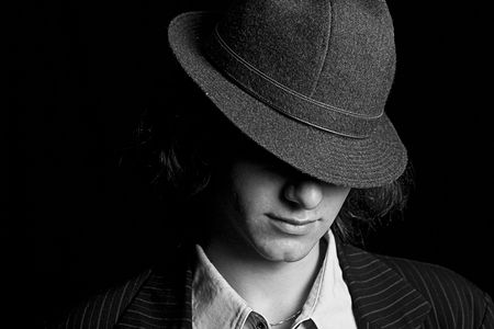 fedora: black and white portrait male teenager with a hat tipped over the eyes