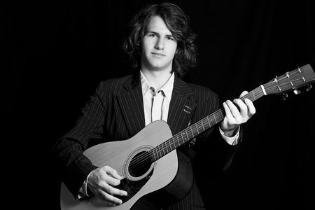 Male teenager folk guitar player with blank expression photo