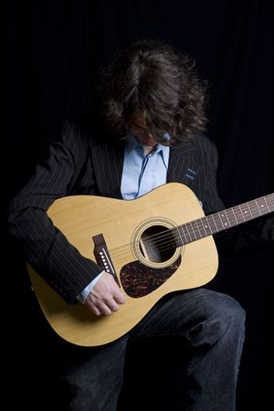 Male teenager folk guitar player bend over laughing photo