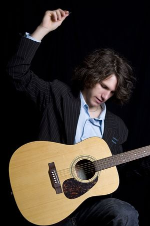 Male teenager folk guitar player about to do a big strum photo