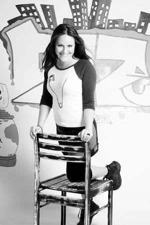 levantandose: Las mujeres j�venes de levantarse de una silla con el fondo de graffiti Foto de archivo