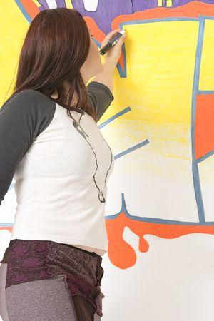 Teen girl drawing a graffiti on a wall Reklamní fotografie