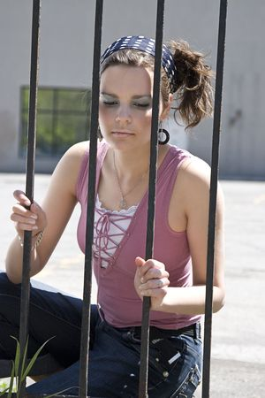 yound women with sad expression behind a fence made out of iron bars
