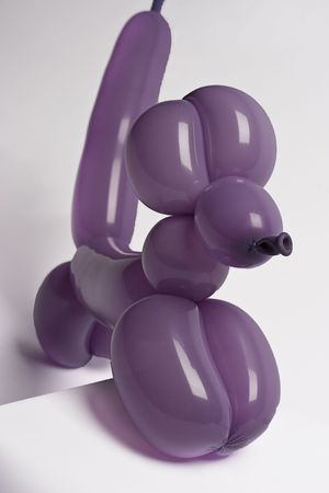 Purple balloon dog climbing a pedestal