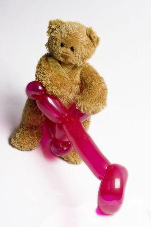 teddy bear sitting on a pink balloon bike Stock Photo - 5318913