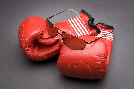 Mens sunglasses place on top of boxing gloves  photo