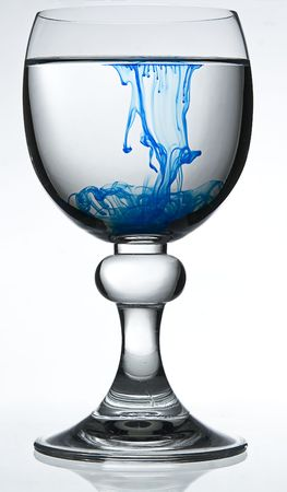wine glass on white background filled with water and blue colorant representing poison