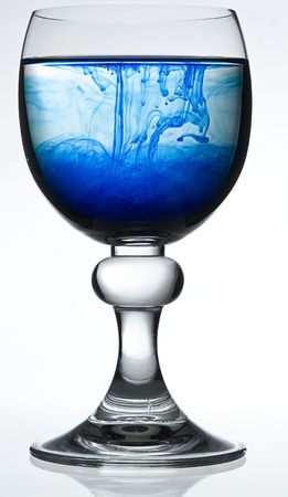 colorant: wine glass on white background filled with water and blue colorant representing poison