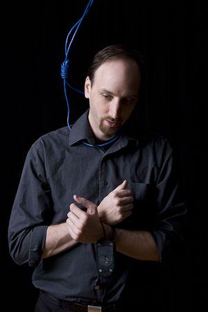 ahorcado: T�cnico de computadoras con las manos atadas y verdugo noeuce hecho con cable de red azul alrededor de su cuello