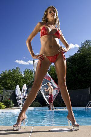 backyard woman: Windsurfer in a pool seen throught the legs of a hot woman in a bikini  Stock Photo