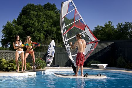 woman squirt: two girl spray a windsufer, in a pool, with water gun Stock Photo