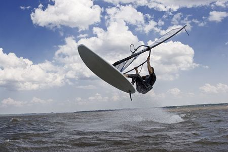 Windsurfer doing a jump trick in the water and catching lots of air