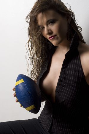 Young and sexy business women showing the inside of her blouse with a blue and yellow football in her hand Stock Photo