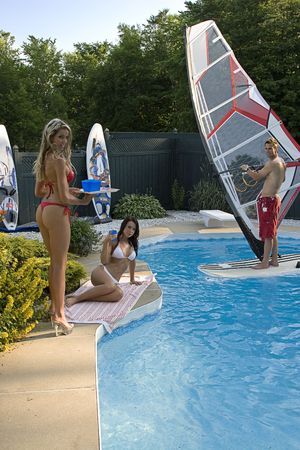 sexy blond in red bikini serving drinks to a sexy brunette women in white bikini by the pool, with windsurfer in the pool Stock Photo - 5626545