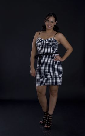 earing: Young latino women in black in white dress with checkers motive Stock Photo
