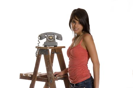 teenage girl standing on wood ladder with old rotary phone